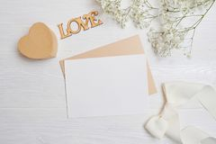 La derisione sulla lettera con una scatola di amore sotto forma di un cuore si trova su una tavola bianca di legno con i fiori de fotografia stock libera da diritti