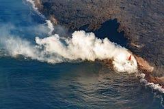 La descripción aérea del área afectada por la manguera de bomberos formó derramamiento de la lava caliente abajo en el océano en  Imagenes de archivo