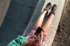 La descripción de una mujer joven utiliza el teléfono en un parque del palacio que se sienta en una fuente - visión desde arri imagen de archivo
