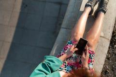 La descripción de una mujer joven utiliza el teléfono en un parque del palacio que se sienta en una fuente - visión desde arri imagen de archivo libre de regalías