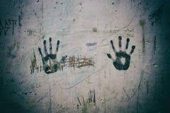La destra e la mano sinistra stampano i segni su una parete misera Fotografie Stock Libere da Diritti