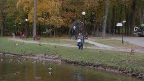 La 10/10/2017 di Russia, Krasnogorsk La mamma e la figlia alimentano gli uccelli nel parco della città durante il giorno video d archivio