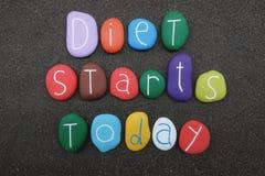 La dieta comienza hoy, lema con las piedras coloreadas sobre la arena volcánica negra imagen de archivo