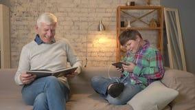 La diferencia de generaciones El hombre mayor se está sentando en el sofá y leyendo un libro, un individuo gordo joven utiliza un metrajes