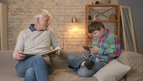 La diferencia de generaciones El hombre mayor se está sentando en el sofá y leyendo un libro, un individuo gordo joven utiliza un almacen de metraje de vídeo