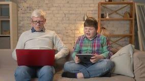 La diferencia de generaciones Hombre mayor con los vidrios que se sientan en el sofá que trabaja en el ordenador portátil, muchac almacen de metraje de vídeo