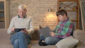 La diferencia de generaciones Un hombre mayor se está sentando en el sofá usando una tableta y los auriculares, un muchacho gordo almacen de metraje de vídeo