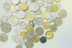 La diffusione delle monete su fondo isolato bianco Fotografia Stock