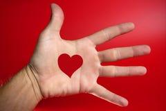 La dimensión de una variable roja del corazón drawed en una mano humana masculina Fotografía de archivo