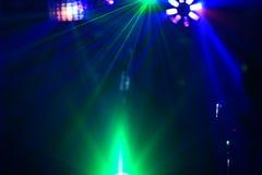 La disco d'éclairage avec les faisceaux lumineux du projecteur et le laser montrent Photos stock