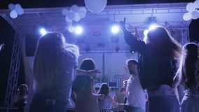 La discoteca dell'estate nelle luci intense, i giovani tipi e le ragazze stanno ballando in night-club, la gioventù con le armi a stock footage