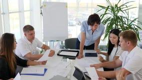La discusión de Businessmans concluye de contrato con los colaboradores en oficina moderna con las ventanas panorámicas grandes metrajes