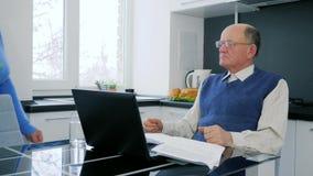 La discussione della famiglia del pensionato, il pagamento anziano della moglie e del marito online con il computer portatile ed