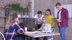 La discussione di affari, giovani colleghe parla con il socio dell'ufficio che lavora al computer stock footage