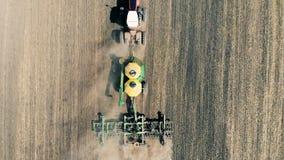 La dispersión del tractor se está moviendo a lo largo del prado y de sembrarlo aéreo almacen de video