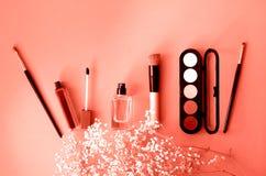 La disposición con color del coral del perfume de los cosméticos y de las mujeres imagen de archivo