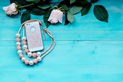 La disposición del fondo de la primavera en un fondo de madera azul con las flores subió y teléfono y gotea los accesorios Fotografía de archivo