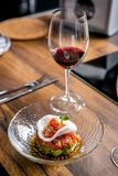 La disposición del plato acabado Tártaro del atún en una placa y un vidrio de vino tinto Clase principal en la cocina El proceso  fotos de archivo