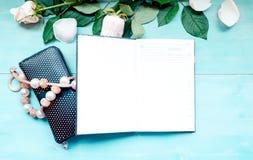 La disposición en un fondo de madera azul con las flores y el planificador diario de los pétalos color de rosa cubre para las not Fotografía de archivo