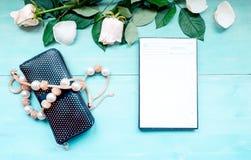 La disposición en un fondo de madera azul con las flores y el planificador diario de los pétalos color de rosa cubre para las not Imagen de archivo libre de regalías