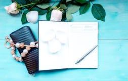 La disposición en un fondo de madera azul con las flores y el planificador diario de los pétalos color de rosa cubre para las not Foto de archivo libre de regalías