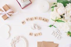 La disposition avec le jour du mariage a orthographié dans les blocs en bois, statuette de deux beaux anges, giftbox, anneaux, ca Photos libres de droits