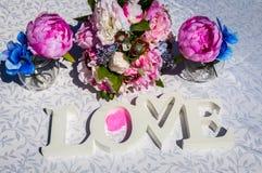 La disposition créative avec les fleurs colorées, les feuilles et le Word AIMENT Lov Photographie stock
