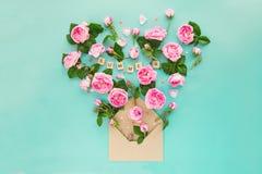La disposition créative avec les fleurs roses de thé rose, les feuilles vertes volent  Images stock