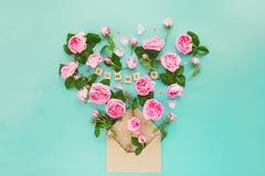La disposition créative avec les fleurs roses de thé rose, feuilles volent hors de l'enveloppe croped de papier de métier dans la Photo stock