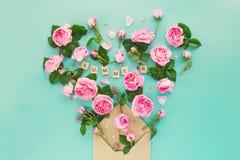 La disposition créative avec les fleurs roses de thé rose, feuilles volent hors de l'enveloppe croped de papier de métier dans la Photographie stock libre de droits