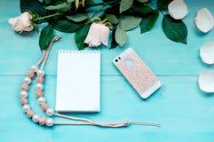 La disposition de ressort sur un fond en bois bleu avec les fleurs et le bloc-notes de pétales couvre pour des disques de télépho Photo libre de droits