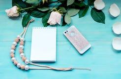 La disposition de ressort sur un fond en bois bleu avec les fleurs et le bloc-notes de pétales couvre pour des disques de télépho Photographie stock libre de droits