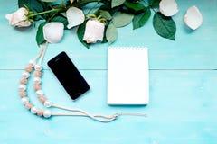 La disposition de ressort sur un fond en bois bleu avec les fleurs et le bloc-notes de pétales de rose couvre pour les notes et l Images stock