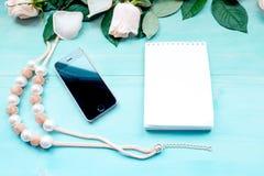 La disposition de ressort sur un fond en bois bleu avec les fleurs et le bloc-notes de pétales de rose couvre pour les notes et l Photographie stock
