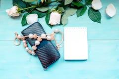 La disposition de ressort sur un fond en bois bleu avec les fleurs et le bloc-notes de pétales de rose couvre pour les notes et l Photo libre de droits