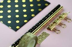 La disposition plate de vue supérieure de l'or sur la papeterie noire rougissent dessus fond rose avec l'espace de copie Photos stock
