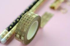 La disposition plate de vue supérieure de l'or sur la papeterie noire rougissent dessus fond rose avec l'espace de copie Photo libre de droits