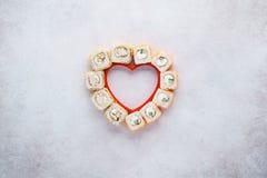 La disposizione creativa fatta di cuore ha modellato l'insieme dei rotoli di sushi immagini stock