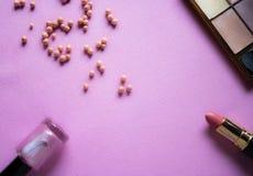 La disposizione del piano di trucco con lo smalto, arrossisce palle della polvere, ombretti e rossetto con l'immagine di sfondo r immagini stock