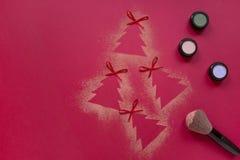La disposizione del piano di trucco degli ombretti di Natale, albero di Natale modella su fondo rosso Fotografie Stock Libere da Diritti