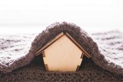La disposizione di concetto di una casa di legno con una sciarpa/offre l'alloggio caldo sul fondo bianco Periodo di riscaldamento immagine stock libera da diritti