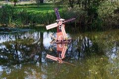 La disposizione di un mulino a vento su uno stagno Fotografia Stock