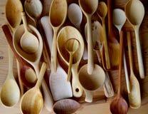 La disposizione di vari passa i cucchiai di legno scolpiti veduti da sopra Fotografia Stock