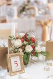 La disposizione floreale dell'avorio e rossa ha preparato per la ricezione, la tavola di nozze con la candela e la regolazione, c Fotografie Stock