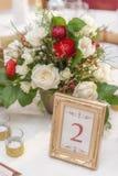 La disposizione floreale dell'avorio e rossa ha preparato per la ricezione, la tavola di nozze con la candela e la regolazione, c Immagine Stock Libera da Diritti