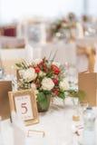 La disposizione floreale dell'avorio e rossa ha preparato per la ricezione, la tavola di nozze con la candela e la regolazione, c Fotografia Stock