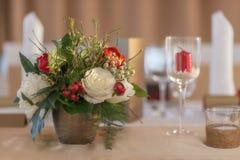 La disposizione floreale dell'avorio e rossa ha preparato per la ricezione, la tavola di nozze con la candela e la regolazione, c Fotografia Stock Libera da Diritti