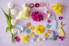 La disposizione piana con la decorazione di Pasqua gradisce i fiori ed i coniglietti immagini stock libere da diritti
