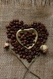 La disposizione piana dei chicchi di caffè arrostiti su una tovaglia con un cuore dorato ha modellato il piattino e la tazza da c Fotografia Stock