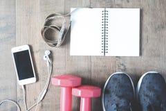 La disposizione piana del taccuino vuoto, il cellulare e l'attrezzatura di sport sopra corteggiano Fotografia Stock Libera da Diritti